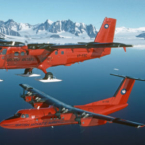 Two red aeroplanes flying above the sea