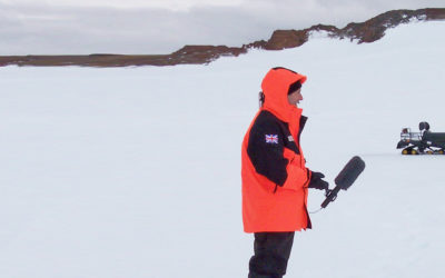 A film crew interviewing a man in an icy landscape