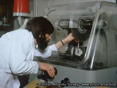A technician cutting a rock sample for thin section production