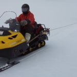 Two-person skidoo team roped together for safe field travel.