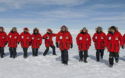 A row of people in red cold weather clothing in an icy landscape