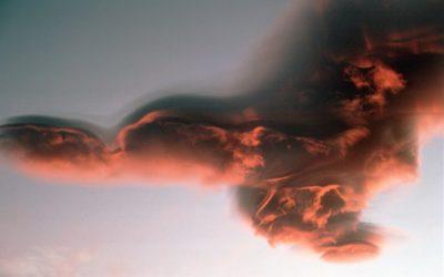 Lenticular alto-cumulus cloud backlit by the setting sun above Jason Peak.