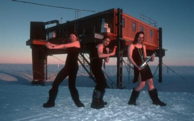 """The Met Angels"" (The Halley wintering Meteorological Team's version of Charlie's Angels) in front of the Simpson (meteorological) Building, Halley.  From left to right: Elaine Cowie (holding an alidade), Annette Faux (holding a portable anemometer), Cathy Moore (holding an Assman psychrometer)."