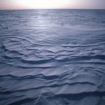 Icescape - Sastrugi in the inland ice sheet, Antarctica. Sastrugi are windblown snow waves formed by the prevailing wind.