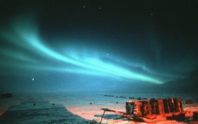 Aurora over Halley with fuel drums on sledge in foreground.  Aurora are caused by the precipitation of charged particles from space towards the magnetic poles driven by plasma winds and magnetic storms.