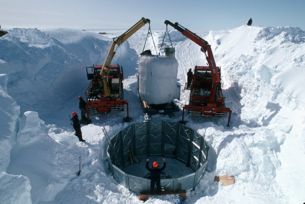 Melt tank being lifted into position by two nodwell cranes at Halley research station.