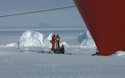 People working on the sea ice next to the hull of a large boat