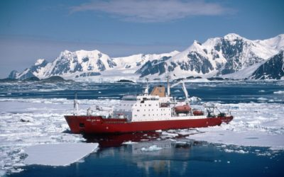 A large ship in the water with a mountain in the snow.