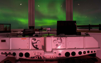 A green aurora out of the windows of a research station