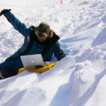 A person lying on top of a snow covered slope.