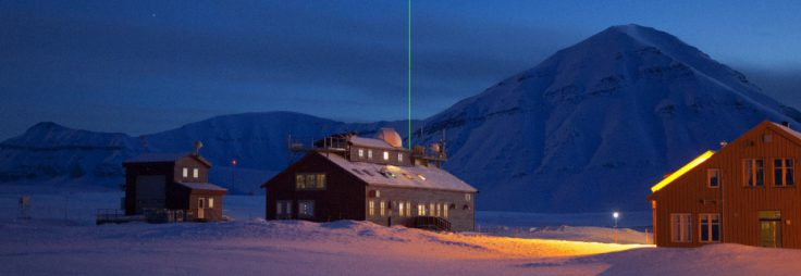 The Koldewey Station at Ny Alesund on Svalbard, is run by the German Alfred Wegener Institute (AWI for the observation of the north polar stratosphere. A variety of optical instruments are installed on and operated from the roof of this building. An infrared spectrometer measures type and quantity of trace gases in the troposphere and stratosphere. A photometer which uses the sun and the moon as light sources measures the optical depth of atmospheric aerosols throughout the year. The concentration of ozone and aerosols in the atmosphere is determined by means of a so-called LIDAR (laser-'radar') seen here clearly above the station. In addition, from the bulding to the left, balloon-borne sensors record temperature, humidity and air pressure, as well as ozone-profiles.