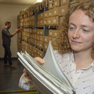 Alysa looking through valuable field party records in the archive at BAS Cambridge