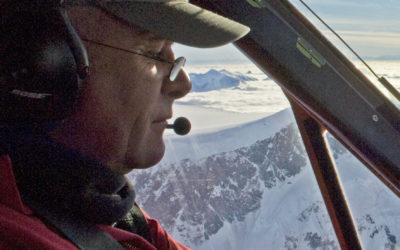 A pilot in the cockpit of an aeroplane flying above mountains