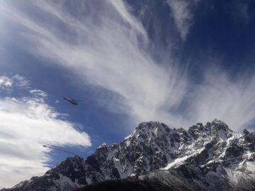 A person flying through the air on top of a mountain