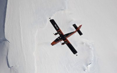 A plane flying through the air above an icy landscape