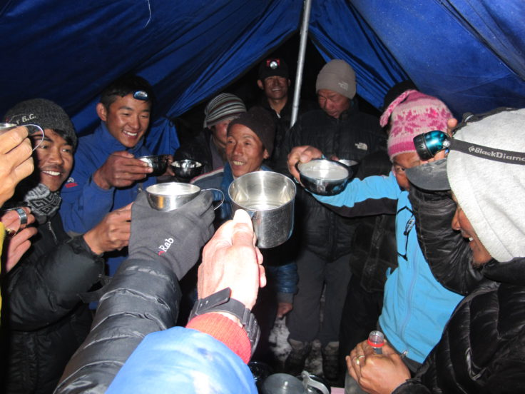 Enjoying a hot mug of chhaang with the guides and porters.