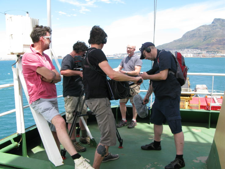 BBC film crew working with Peter Gibbs aboard the RRS Ernest Shackleton as the ship departs Cape Town