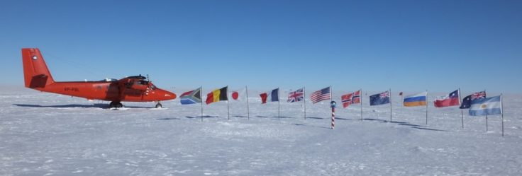 Survey aircraft VP-FBL enjoying her photo shoot at the ceremonial South Pole with the flags of all the original Antarctic Treaty nations