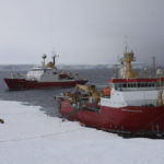 Two large ships at an icy coastline