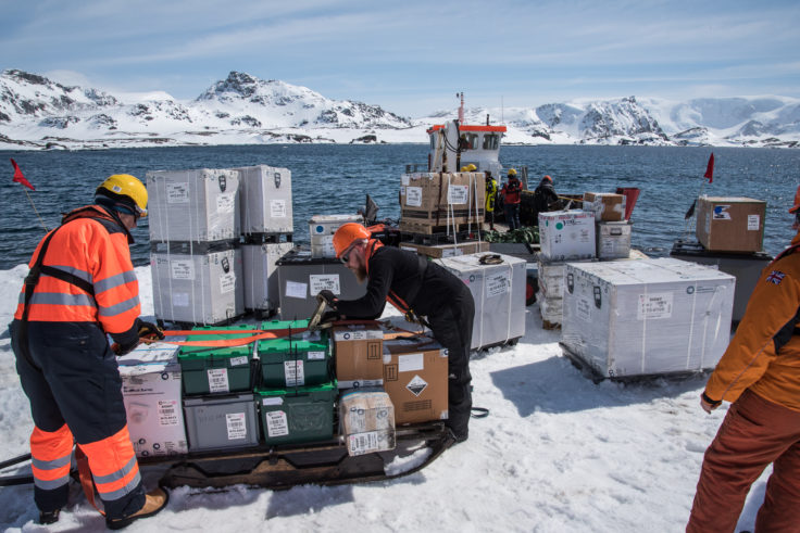 JCR staff unload the cargo tender and re-load cargo onto sledges to be hauled by ski-doo to the station
