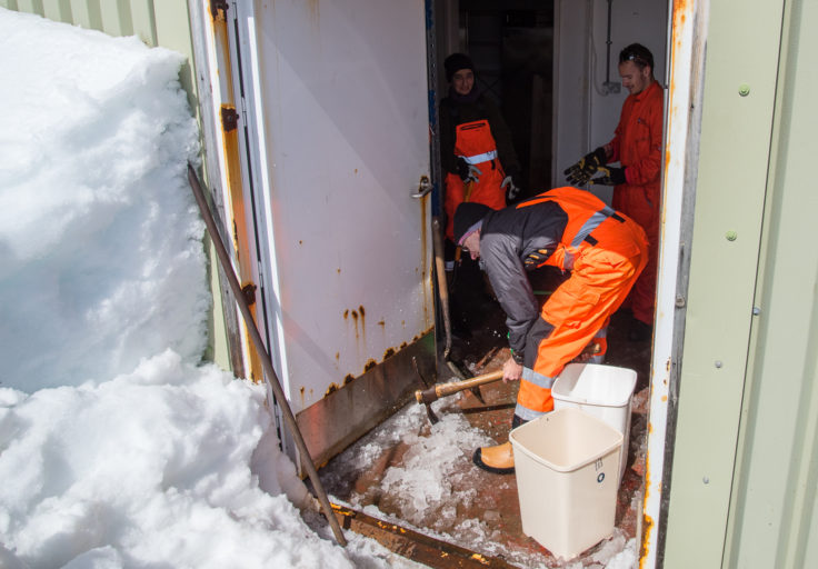 JCR staff helping out with opening up of the base buildings. Here they remove ice from the floor of the food store
