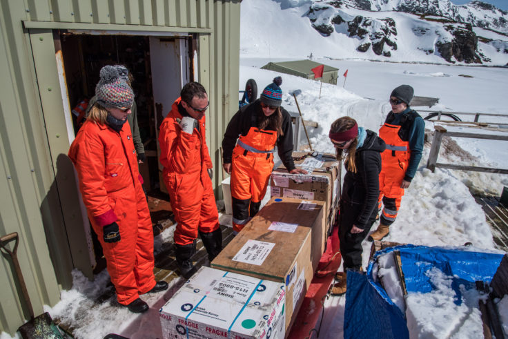 Staff prepare to unload a sledge of cargo ski-doo'd up from shore to the Top Store