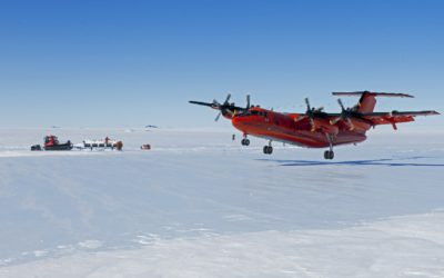 The British Antarctic Survey Dash 7 aircraft lands at the Sky Blu runway. In the background is a Piston Bully vehicle & trailer on which are white travel boxes full of ice cores that are being taken north to Rothera Research Station on the first leg of their journey to analytical Labs in Europe. Such Ice cores are critical to our understanding of past climate and predictions of future change.