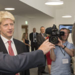 Jo johnson wearing a suit and tie holding a cell phone.