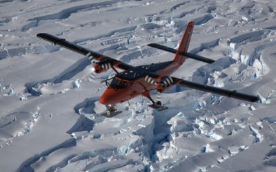 A aeroplace flying over a snowy landscape
