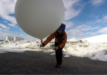A person holding a weather balloon