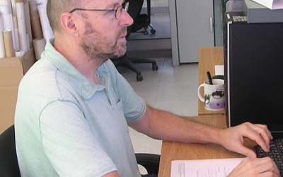 A man sitting at a table using a laptop.
