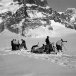A group of people riding on the back of a horse in the snow.