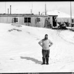 Lewis 'Chippy' Ashton standing in front of the recently completed Bransfield House, Port Lockroy, 26th October 1944. (Photographer: E. Mackenzie (I.M. Lamb). Archives ref: AD6/19/1/A52)