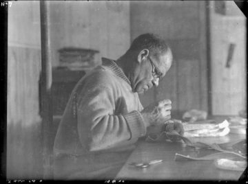 Lt. Cdr. James Marr at work mending webbing, Bransfield House, Port Lockroy, 18th June 1944. Photographer: I M Lamb. Archive ref: AD6/19/1/A7