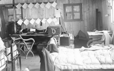 An old photo of a living room filled with furniture and a bed.