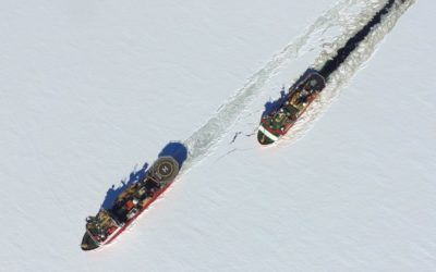 Two large boats saliing through sea ice