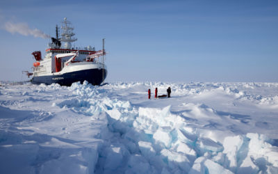 A large boat in the sea ice with people in the foreground
