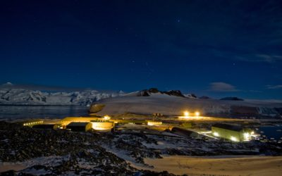A research base lit up in an icy landscape in the dark