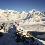 People on a snowy mountain range holding a rainbow flag