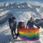 Three people on a snowy mountain top holding a rainbow flag
