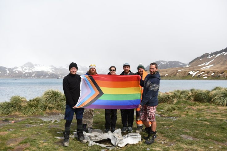 A team standing with a progress pride flag