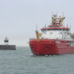 Large red ship arrives into a port
