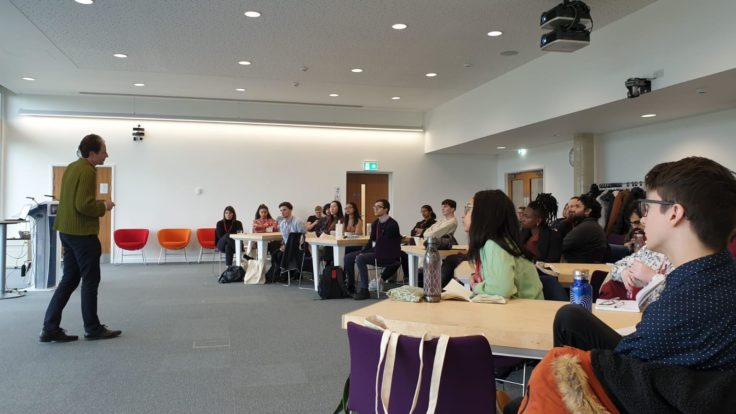 A group of students listening to a talk in a conference room