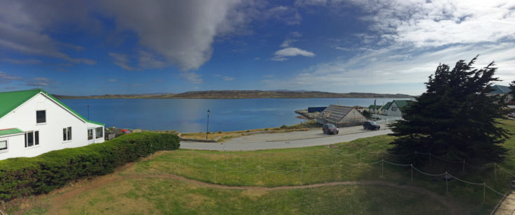 A body of water with grassy area in front of a building at Port Stanley, Falklands