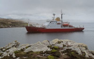 Large red ship in a body of water with rocks in the foreground