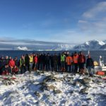 A group of people standing on top of a snow covered mountain