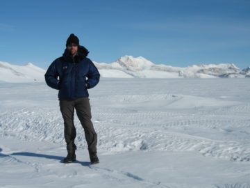 A man standing on top of a snow covered slope