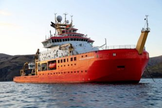 A large red ship in a large body of water