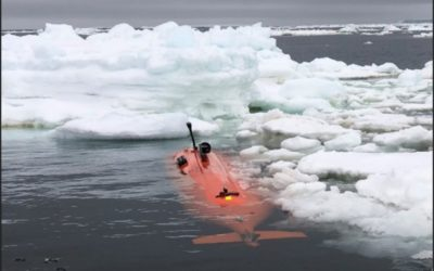 An orange submersible is partly visible in the water, with ice floating next to it