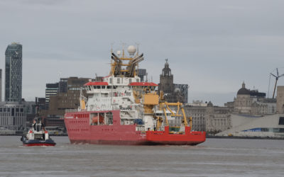 A large red ship on a body of water, with Liverpool city in the background